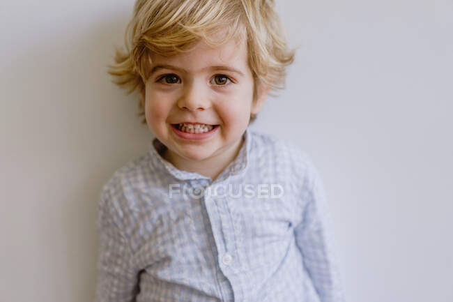 Adorable little kid wearing casual shirt smiling and looking at camera on white background of studio — Stock Photo