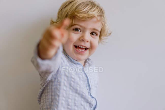 Очаровательный маленький ребенок в повседневной рубашке улыбается и смотрит в камеру на белом фоне студии — стоковое фото
