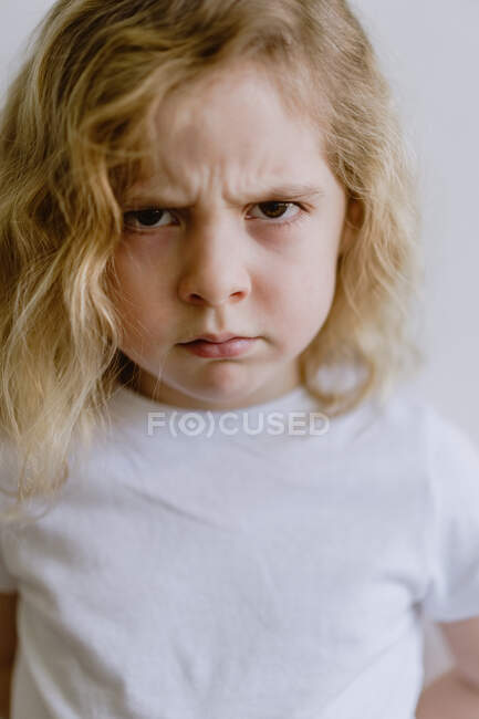 Disappointed little child in casual t shirt looking at camera on white background in studio — Stock Photo