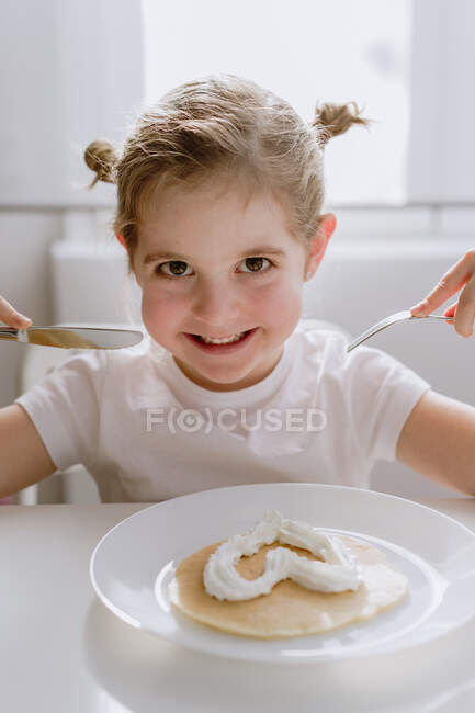 Захоплена маленька дитина в повсякденній футболці сидить за столом з тарілкою смачного млинця, прикрашеного збитими вершками серцеподібної форми і весело дивлячись на камеру. — стокове фото