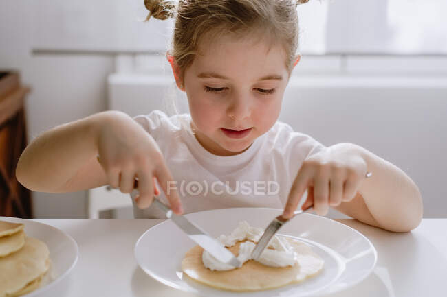 Thrilled little child in casual t shirt sitting at table with plate of tasty pancake garnished with heart shaped whipped cream — Stock Photo