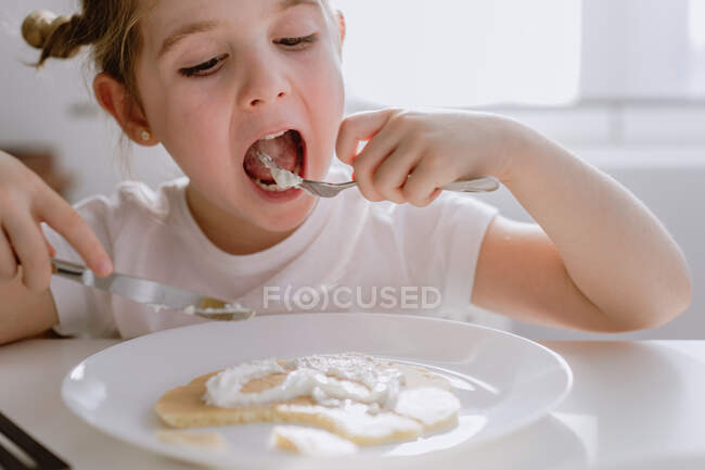 Захоплена маленька дитина у звичайній футболці сидить за столом з тарілкою смачного млинця, прикрашеного збитим вершками у формі серця. — стокове фото
