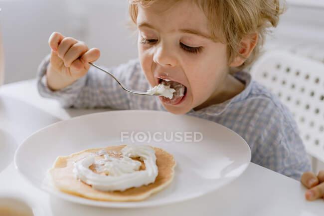 Приємна дитина їсть смачний млинець з збитими вершками, сидячи за столом у яскравій кухні і снідаючи. — стокове фото
