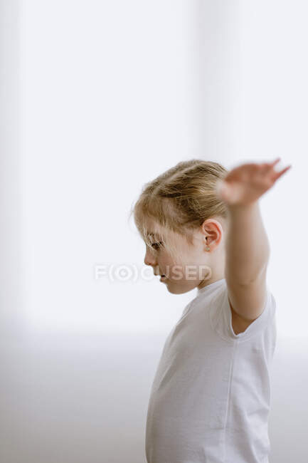 Side view of content little kid in casual outfit standing in bright apartment and stretching arms during warm up — Stock Photo