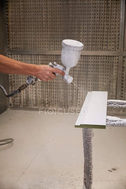 Focused workman using airbrush for applying flame retardant to wood detail ensuring fire protection in carpentry workshop — Stock Photo