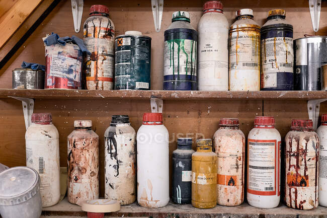 Colección de botellas y frascos multicolores de plástico y metal de productos químicos especiales para trabajos de carpintería en estantes de madera en un taller contemporáneo - foto de stock
