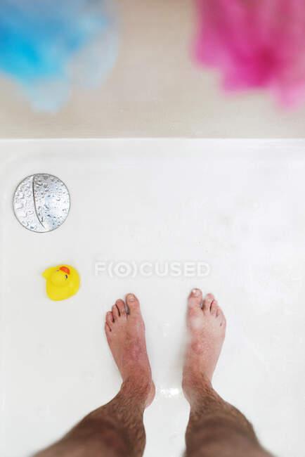 Верхній вигляд нерозпізнаного чоловіка з мильною піною на ногах стоїть у ванній з жовтою гумовою качкою, розташованою неподалік. — стокове фото