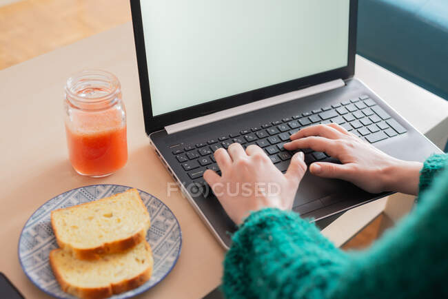 From above of female freelancer sitting in living room at table with toasts and fresh juice while working online on project and using netbook — Stock Photo