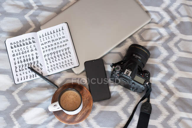 Top view of opened notepad and cup of hot coffee composed with photo camera and laptop on cozy bed — Stock Photo
