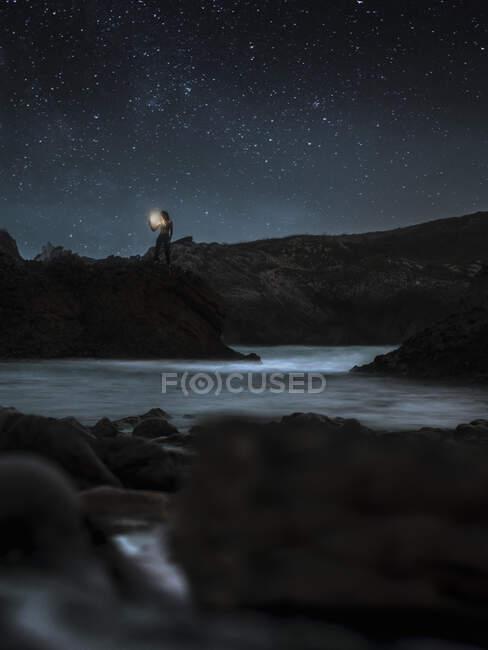 Silueta de viajero de pie con linterna en la orilla rocosa del río y admirando misteriosos paisajes de aguas tranquilas durante la noche estrellada en las tierras altas - foto de stock