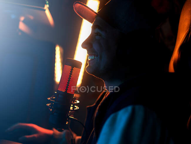 Side view of trendy focused millennial male artist in cap and hoodie performing song while standing alone with eyes closed and touching headphones beside professional mic against bright yellow longed lamp in dark studio — Stock Photo