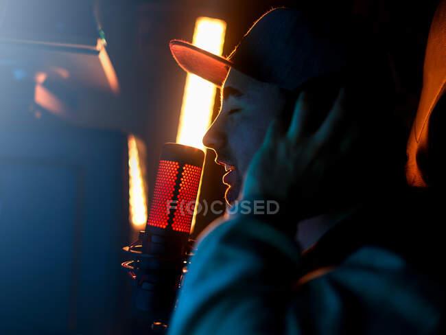 Vista lateral del artista masculino milenario enfocado de moda en gorra y sudadera con capucha interpretando la canción mientras está parado solo con los ojos cerrados y tocando los auriculares junto al micrófono profesional contra la lámpara anhelada de color amarillo brillante en el estudio oscuro - foto de stock