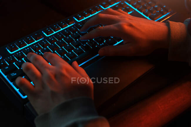 High angle of unrecognizable man in casual clothes typing on black keyboard with comfortable blue backlight while using computer in dark room with dim light at night — Stock Photo