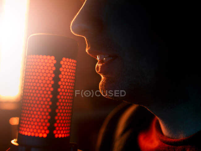Side view cropped unrecognizable millennial male artist performing song alone beside professional mic against bright yellow longed lamp in dark studio — Stock Photo