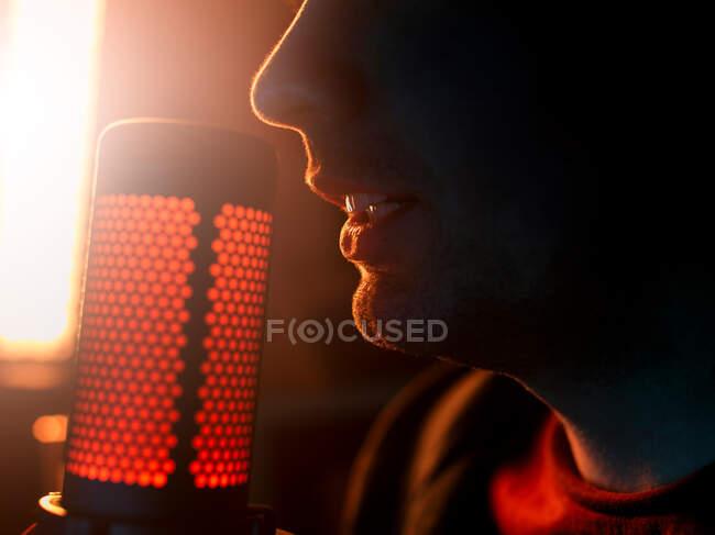 Vista lateral recortado irreconocible artista masculino milenario realizar canción solo al lado de micrófono profesional contra la lámpara anhelada amarillo brillante en el estudio oscuro - foto de stock