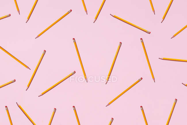 Top view of seamless background of pencils chaotically scattered on pink surface — Stock Photo