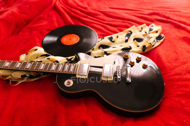 High angle of old fashioned vinyl disc and modern electric guitar placed on retro dress in apartment — Stock Photo