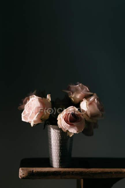 Свіжі рожеві троянди у вінтажній вазі, розміщені на дерев
