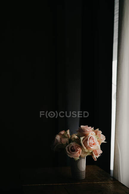 Blooming fresh pink roses in vintage vase placed on wooden table at black wall near windows in modern apartment — Stock Photo