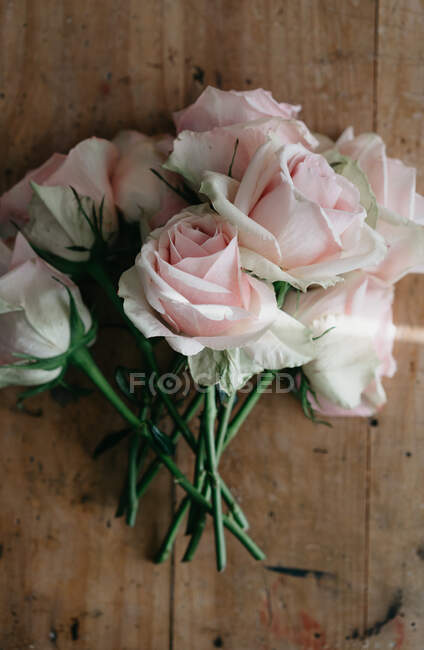 Top view of bunch of fresh pink roses placed on shabby wooden table in light room — Stock Photo