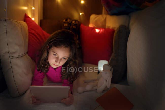 Ruhige kleine Mädchen liegen in gemütlichen Haus mit Kissen und Decke mit glühenden Lampen und Browsing-Tablet gemacht, während die Zeit zu Hause verbringen — Stockfoto