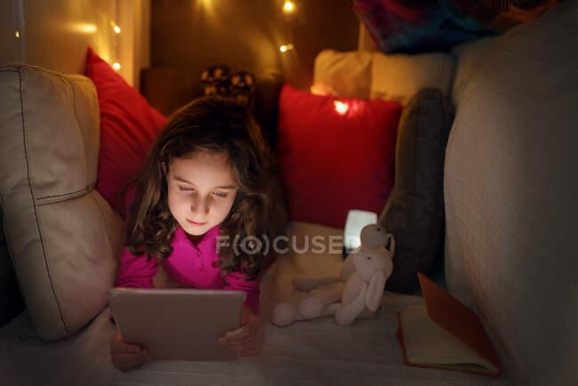 Menina calma deitada dentro da casa acolhedora feita com almofadas e cobertor com lâmpadas brilhantes e tablet de navegação enquanto passa o tempo em casa — Fotografia de Stock