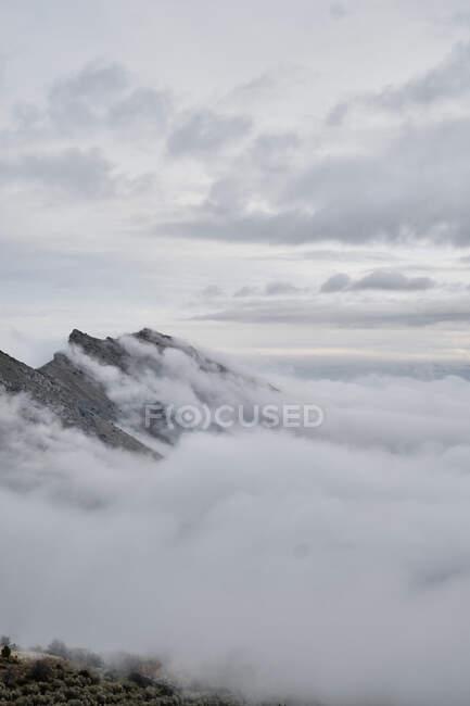 Incredibile vista sulle cime delle montagne coperte di nebbia e nuvole — Foto stock