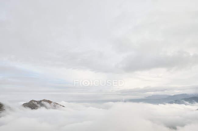 Increíble vista de los picos de montaña cubiertos de niebla y nubes - foto de stock