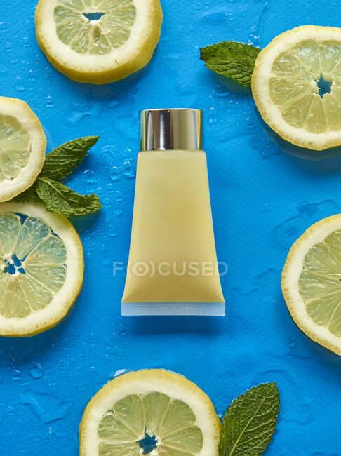 Верхний вид стеклянной бутылки в окружении свежих ломтиков лимона с листьями мяты на синем фоне, покрытых прозрачными капельками воды — стоковое фото