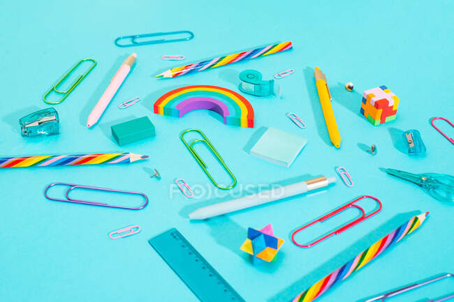 Close-up view of a bunch of colorful school supplies over blue background — Stock Photo