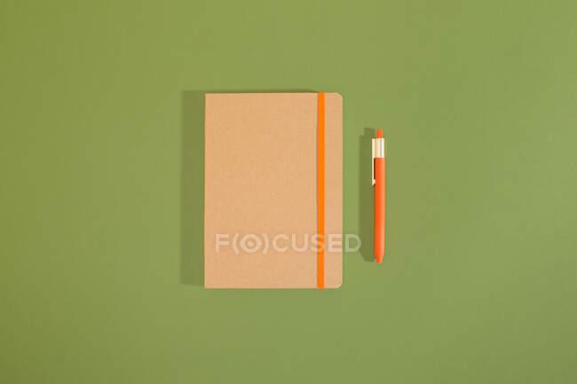 Vista dall'alto di una composizione minimale di quaderno e matita riciclati con sfondo verde. — Foto stock