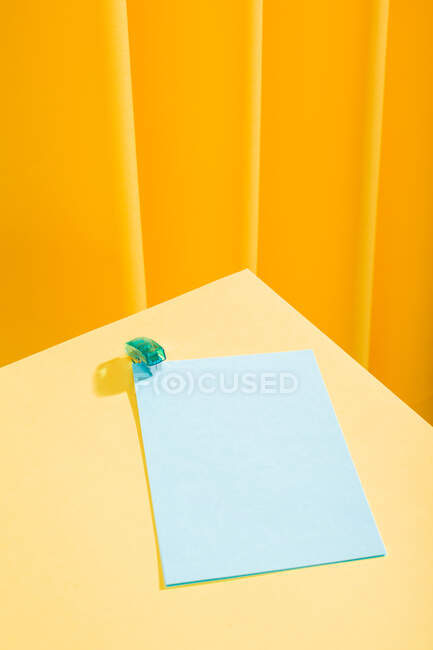 Little blue stapler stapling blue papers over yellow table — Stock Photo