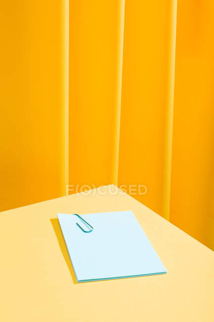Front view of a minimal composition of a blue paper with a blue paperclip over a yellow table. — Stock Photo