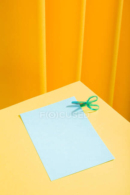 Blue little scissor cutting blue papers over a yellow table — Stock Photo
