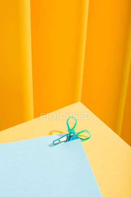 Close-up view of blue tiny scissor cutting a blue paper over a yellow table — Stock Photo