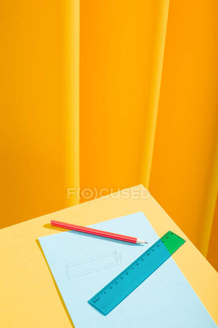 Lápis vermelho e régua azul com papéis e desenha sobre uma mesa amarela — Fotografia de Stock