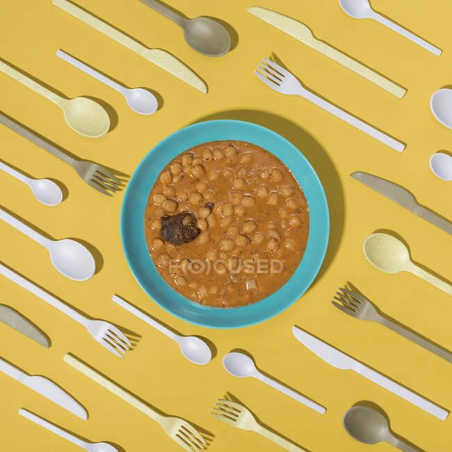 Vista superior de composición mínima de Callos con un montón de cubiertos sobre fondo amarillo - foto de stock