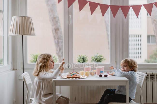 Веселі маленькі діти в повсякденному одязі сидять за дерев'яним столом біля вікна і їдять солодкий торт під час відпочинку. — стокове фото