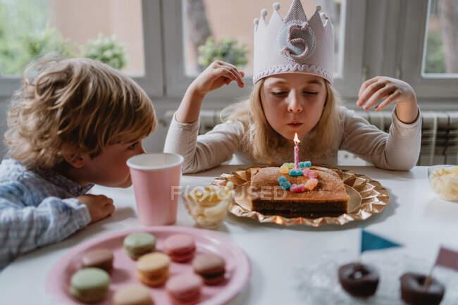 Щаслива маленька дівчинка в повсякденному одязі і з короною ввімкнути свічку на торт до дня народження, сидячи за дерев'яним столом під час вечірки. — стокове фото