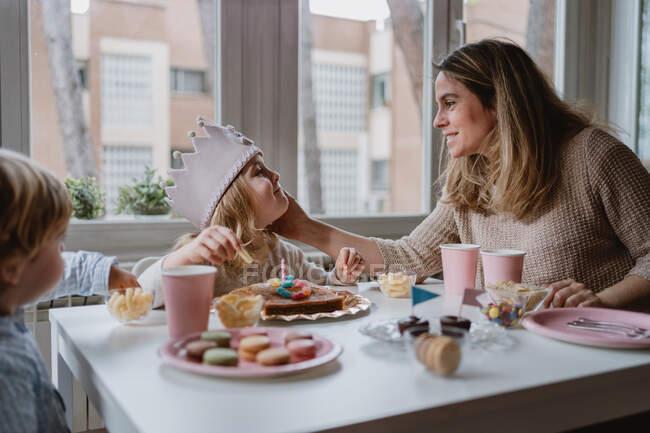 Позитивна мати в повсякденному одязі сидить за дерев'яним столом і розмовляє з дітьми, які святкують день народження вдома. — стокове фото