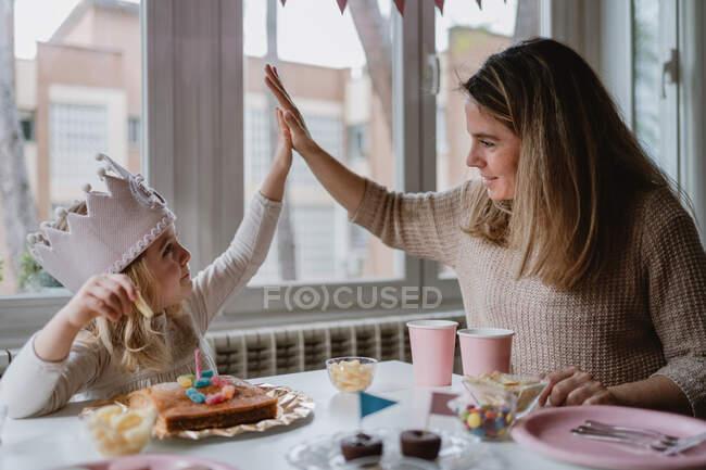 Мила дівчинка в повсякденному одязі і паперовій короні дає п'ять матерів, сидячи за столом і споживаючи смачну їжу під час відпустки. — стокове фото