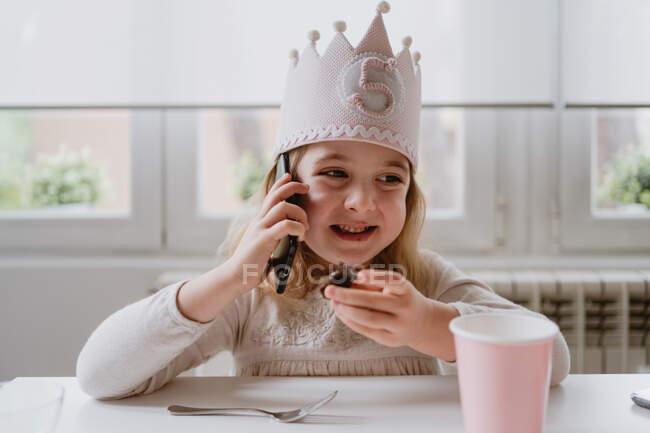 Щаслива маленька дівчинка в повсякденному одязі і святковій короні сидить за столом і розмовляє на смартфоні, поки їсть солодкі цукерки вдома. — стокове фото