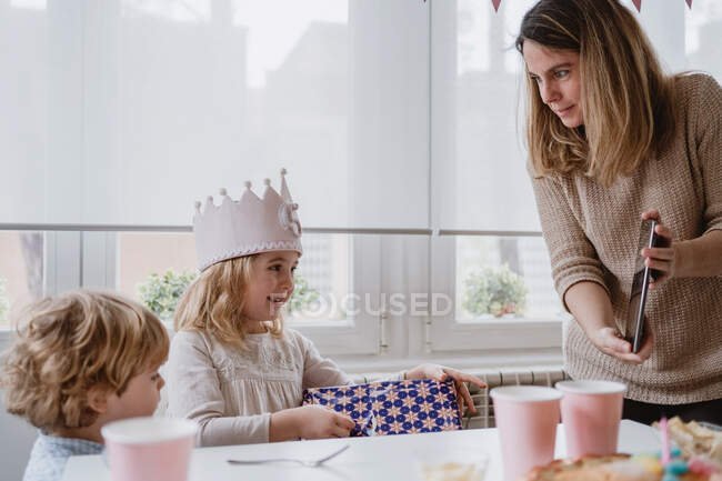 Возбужденная очаровательная девушка в короне ручной работы разворачивая подарочную коробку во время празднования дня рождения дома — стоковое фото