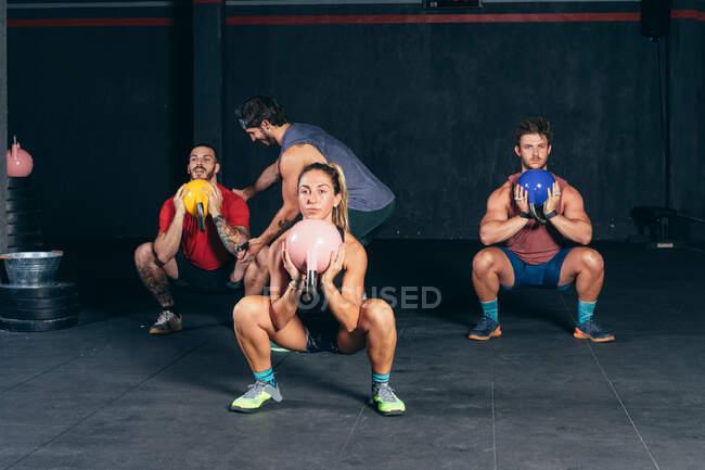 Компания мускулистых спортсменов, приседающих с гирями во время интенсивной тренировки под наблюдением профессионального инструктора — стоковое фото