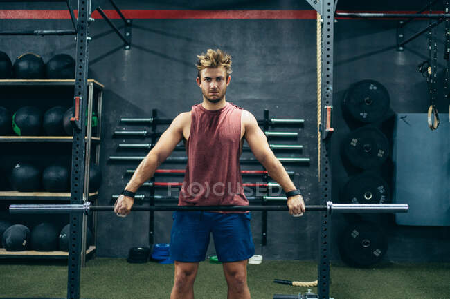 Сильный спортсмен делает упражнения с штангой во время тренировки в современном спортзале и смотрит в камеру — стоковое фото
