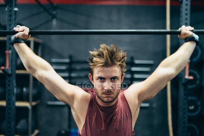 Сильний спортсмен виконує вправи з бараниною, працюючи в сучасному спортзалі і дивлячись на камеру. — Stock Photo