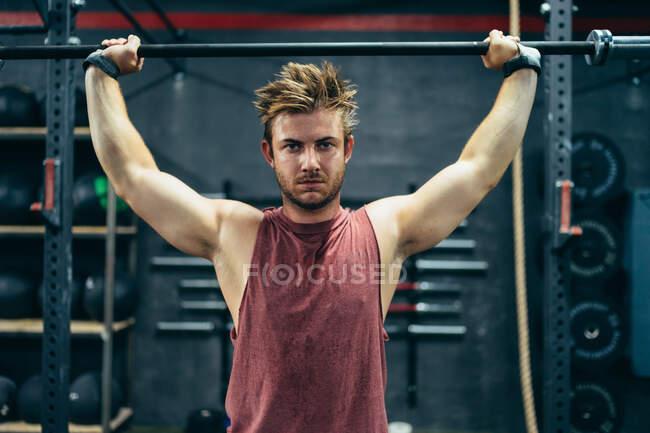 Fuerte atleta masculino haciendo ejercicios con barra de pesas mientras hace ejercicio en el gimnasio moderno y mirando a la cámara - foto de stock