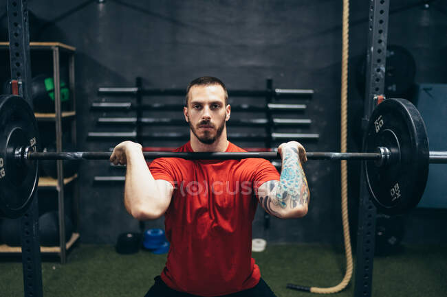 Confident male athlete in sports t shirt lifting barbell over head during training and looking at camera — Stock Photo