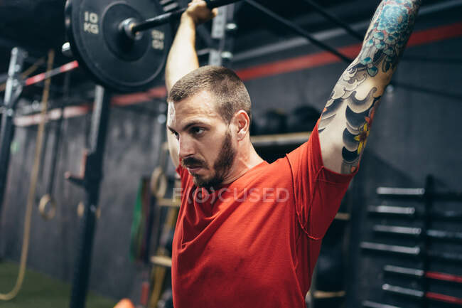 Side view of confident male athlete in sports t shirt lifting barbell over head during training and looking away — Stock Photo