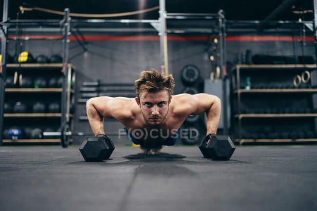 Potente atleta masculino sin camisa haciendo flexiones y usando pesas mientras entrena en el gimnasio y mira la cámara - foto de stock